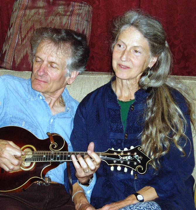 Mike Seeger playing some mandolin at a party alongside his wife, Alexia Smith.