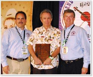 Dr. Perry F. Harris Award winner Buck White (center) with Grand Master Fiddler Championship president Howard Harris (right) and GMFC vice chairman Ed Carnes. Photo: Randall Franks/randallfranks.com