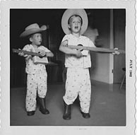 Decked out in western ensemble PJs, Paul on the left, playing left-handed backup guitar to big brother Jeff's lead singing. Photo and cigar-box guitars by their father, John Glasse. Click to enlarge.